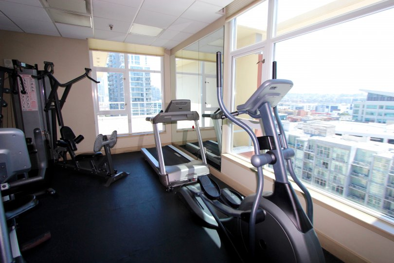 Well-appointed fitness room with massive windows overlooking the city at Diamond Terrace in Downtown San Diego, California.