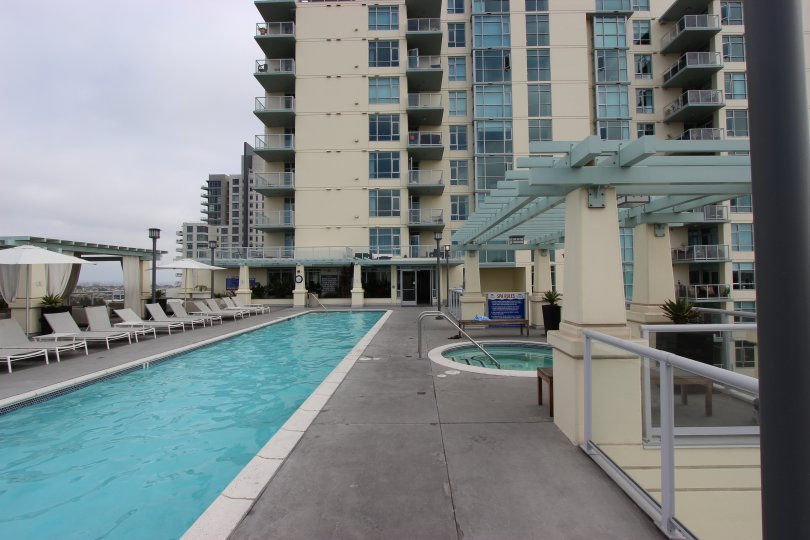 A long narrow pool sits on a rooftop terrace on a cloudy day at Discovery condos