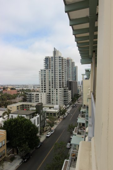 Balcony Street view of the Discovery Condos Downtown San Diego California with parked cars by sidewalks