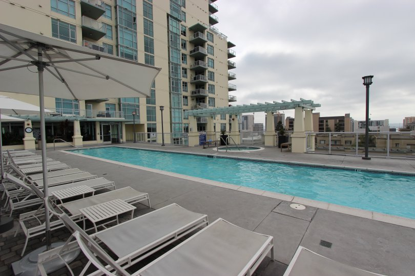 A long, thin pool sits under a dark cloudy sky at Discovery condos