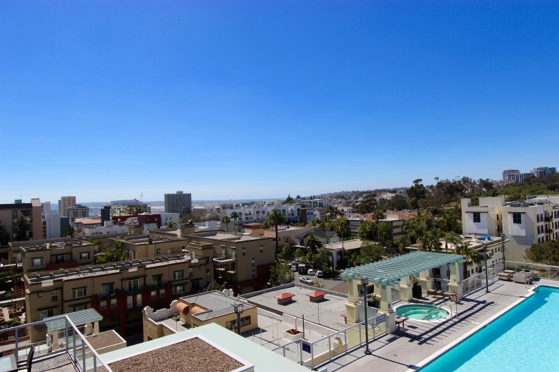 Downtown San Diego building in the Discovery community in California. The view from the roof of a building of a large part of the city and blue sky in the background. Pool and hot tub are pictured on the bottom right.