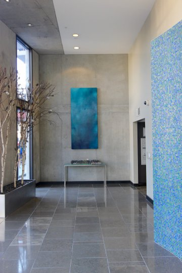 A blue and white tiled art piece in a hallway at DOMA condos