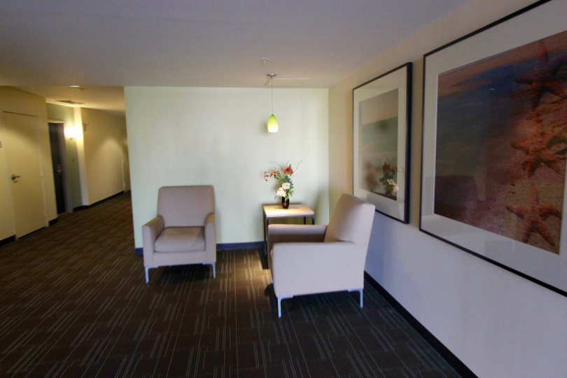 Large waiting room with white walls and beautiful pictures and two seats.