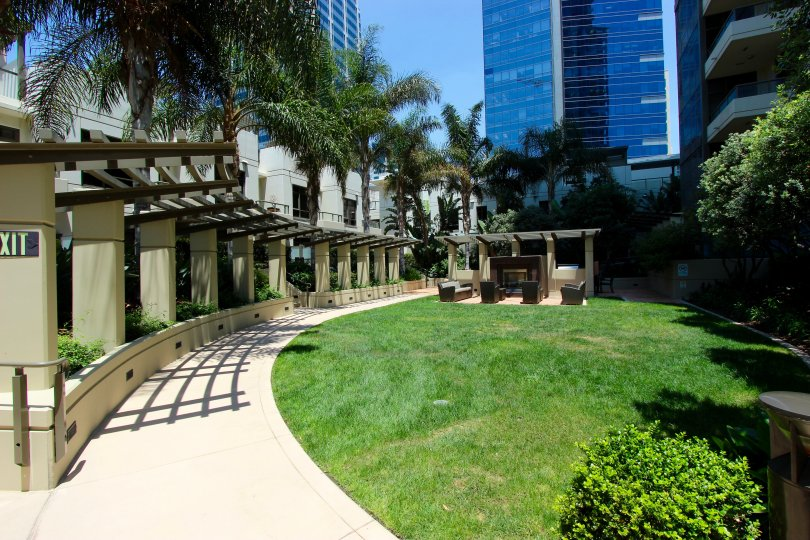 Long walkway along a green field with trees & flowers at Electra in downtown San Diego