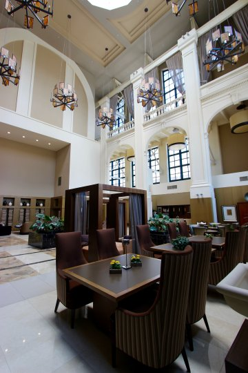 A view of the lobby of the Electra building with modern light fixtures, cathedral ceiling, and skylights over comfortable dining tables.
