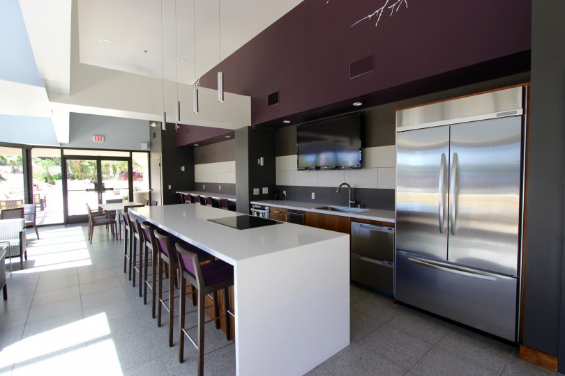 An interior view of the sleek and modern dining lounge at the Harbor Club with stainless steel appliances and plum colored accents.