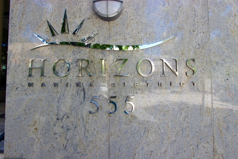 A shiny chrome sign on a marble wall inside Horizons Community in downtown San Diego CA