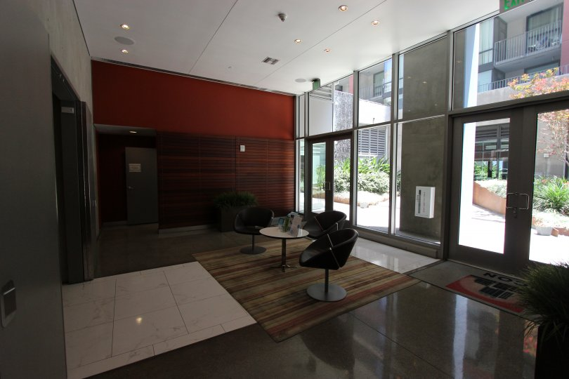 This the lobby of the hotel which has the beautiful glass doors and chairs and also the plants in Icon neighborhood of Downtown San Diego