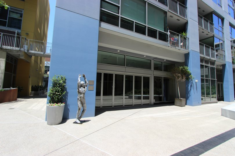 A statue of a man reaching for the sky sits in front of a blue wall in a courtyard at Icon.