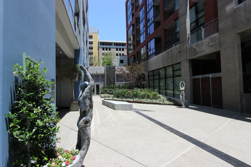 A sunny day in the Icon with some huge buildings and a sculpture.