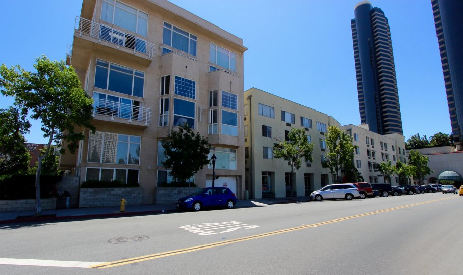 Fron. viewt of Island Lofts Condominium Downtown San Diego California with trees and parked cars