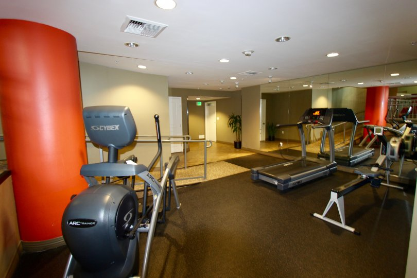 A treadmill facing a mirror allows the user to watch as they work out in the fitness room at La Vita