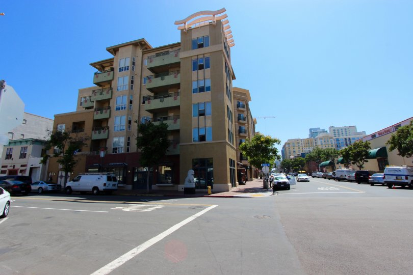 A sunny and cheerful day at the Pacific Terrace with a panoramic view of the classy and contemporary building and the tree-streets with the shops and parked cars