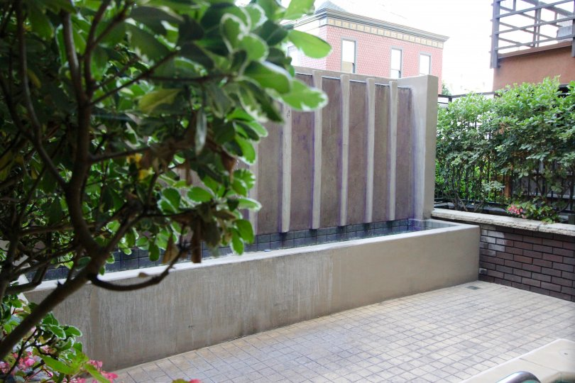 A view of the water feature on a terrace with a brick wall at Park Blvd East.