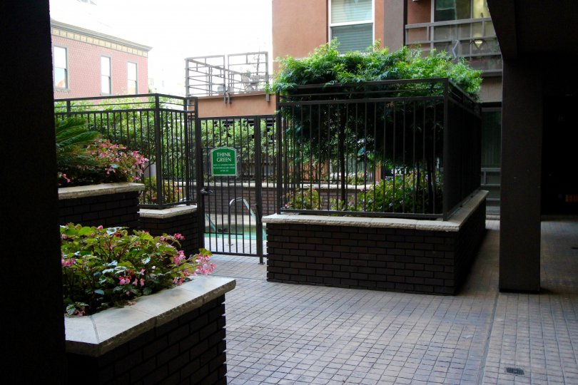 A sunny day in the area of Park Blvd East, outside, fennce, gated entrance, flowers, trees, brick