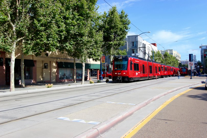 A bright red train of Park Blvd West in Downtown San Diego, CA
