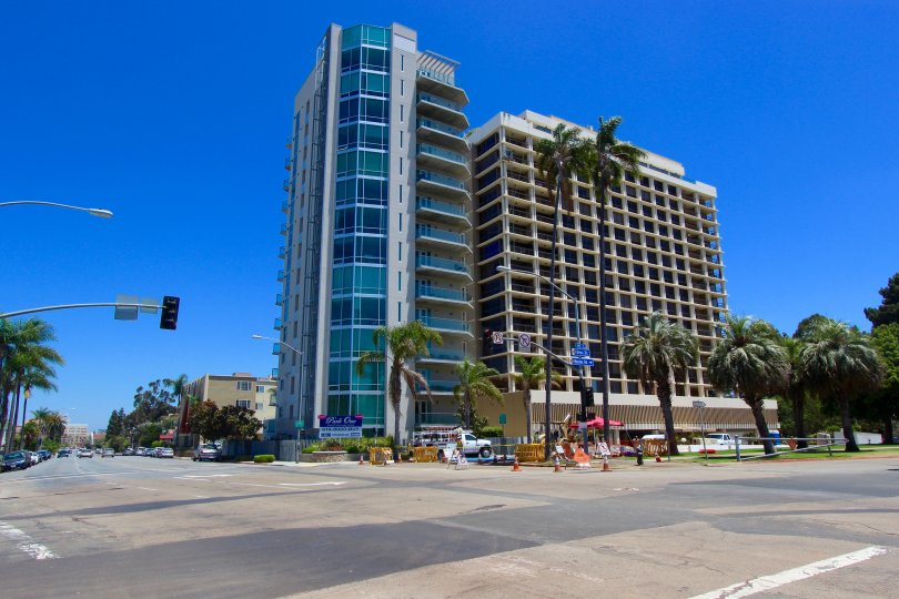 Picture of a San Diego High Rise on the corner of a street. Blue sky in the back and palm trees surrounding the building.