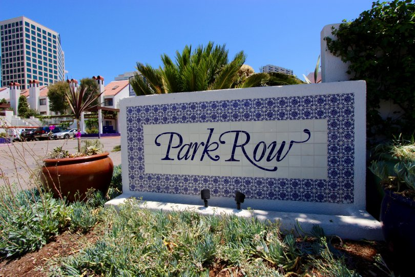 A white and blue sign with decorative plants at Park Row in downtown San Diego, CA