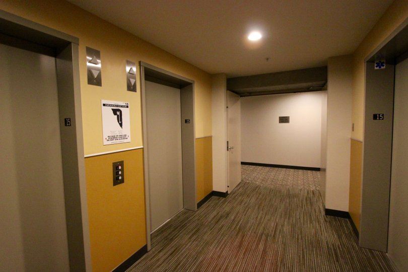 Elevators face each other in a tan and mustard hallway at Smart Corner.