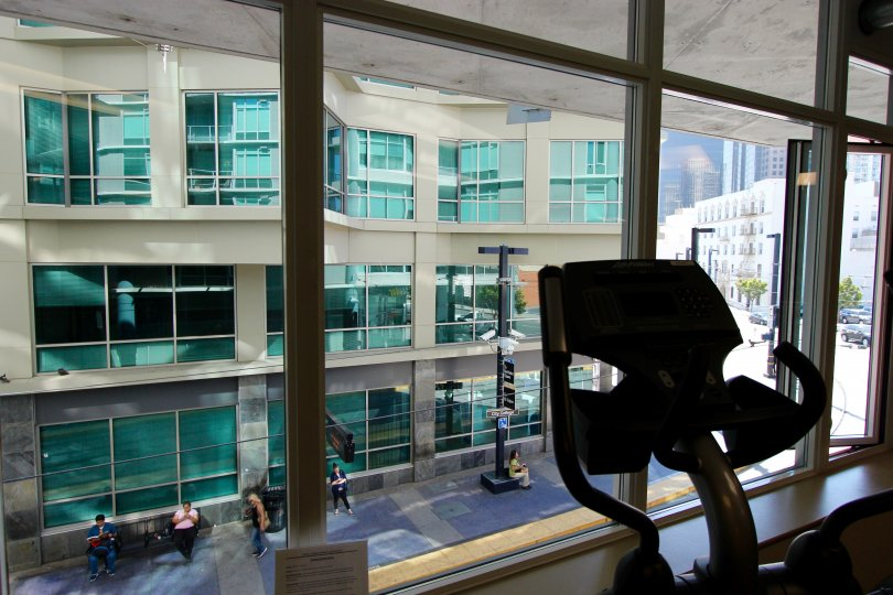 A sunny day in the area of Smart Corner, workout room, eliptical machine, people, outside, windows