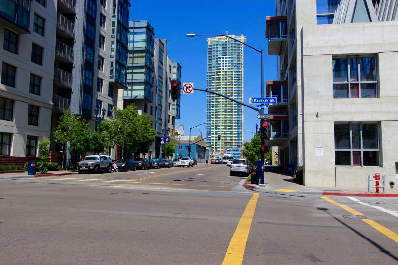 A street view of Smart Corner in San Diego, CA on a clear and sunny day. The image shows a street corner with buildings and a few cars at an intersection.