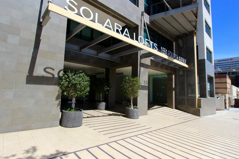 A sunny day in the area of Solara Lofts, outside, entrance, potted plants, sidewalk, highrise