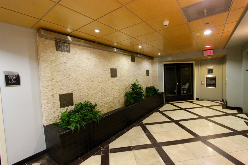 Stone walled and brown and white tilled lobby with yellow ceiling.