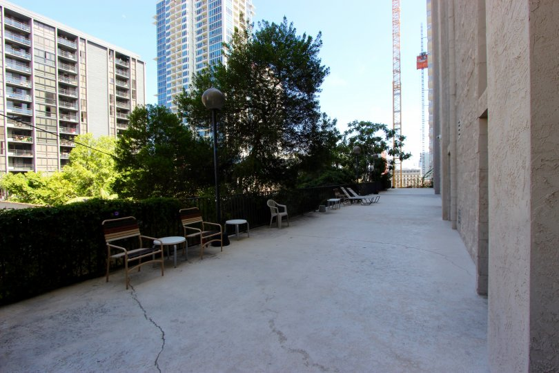 A sunny day in the area of Symphony Terrace, sidewalk, outside, tree, chair, table, highrise