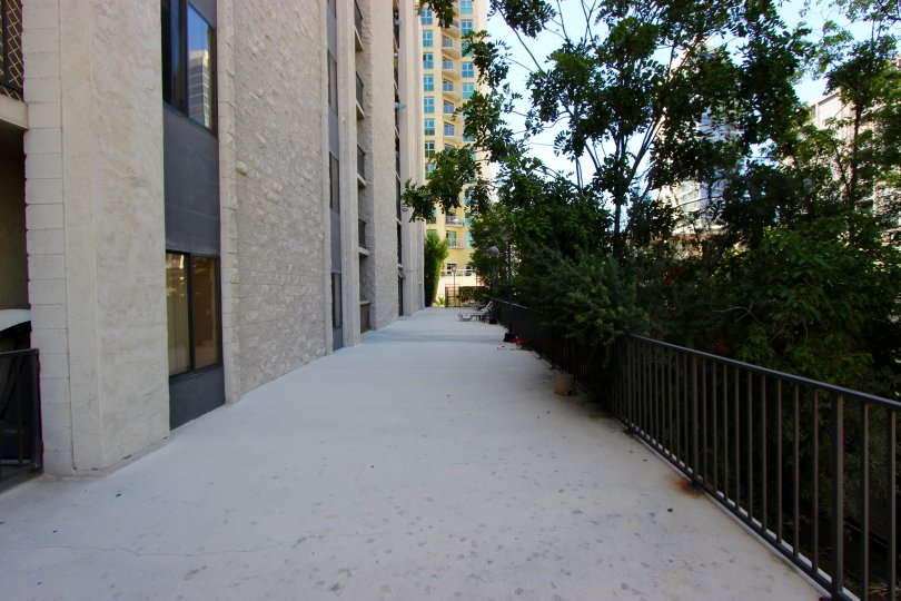 A long, shaded walkway sits next to a gate at the Symphony Terrace condos
