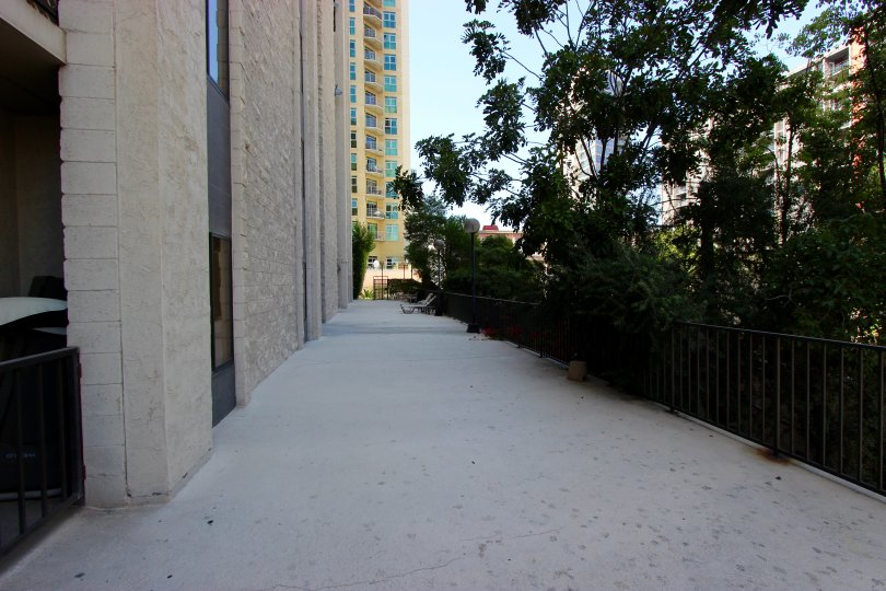 A sunny day in the area of Symphony Terrace, sidewalk, fence, trees, high rise apartments