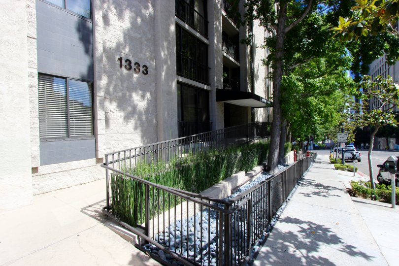 A sunny day in the area of Symphony Terrace, outside, fence, sidewalk, tree, high rise, cars, street