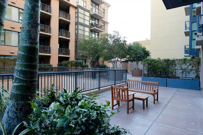 A sunny day in the area of Trellis, outside, fence, table, chair, bench, tree, balcony