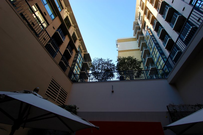 The view upward from a courtyard with umbrellas at Trellis in downtown San Diego, CA
