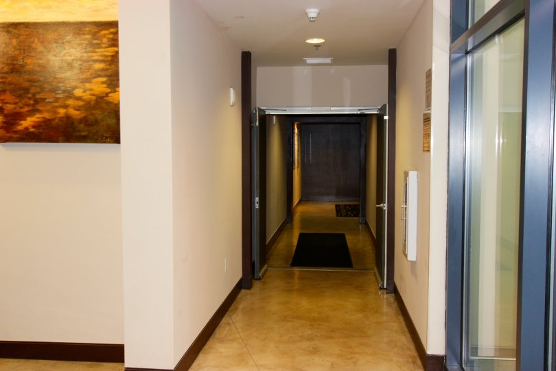 Hallway with art, soft lighting, and large entry doors at Trellis in Downtown San Diego, California