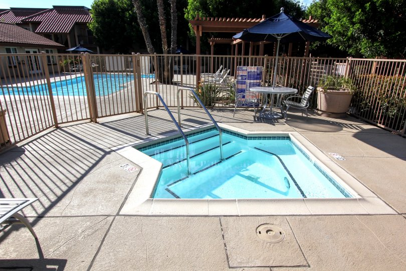 A pool view in the Cottage Villas with swimming pool and out door chairs.