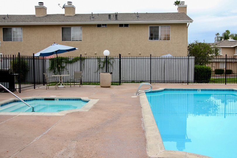VERY BEAUTIFUL HOUSE. IN FRONT OF IT THERE ARE FOUR SMALL TREES. AND THERE IS A ROAD, VERY CLEAN. AND THERE IS A POOL.