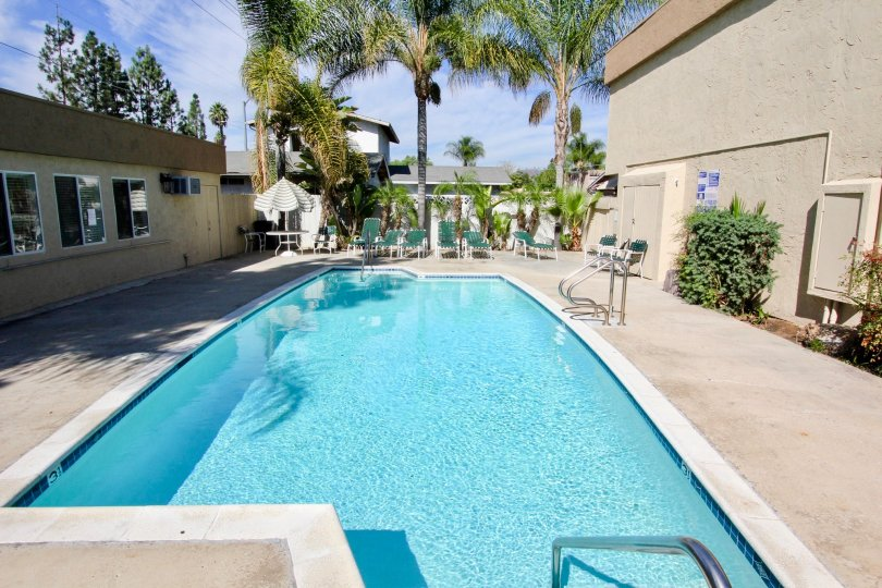 Swimming pool with lawn chairs and clubhouse at Mollison Estates in El Cajon California
