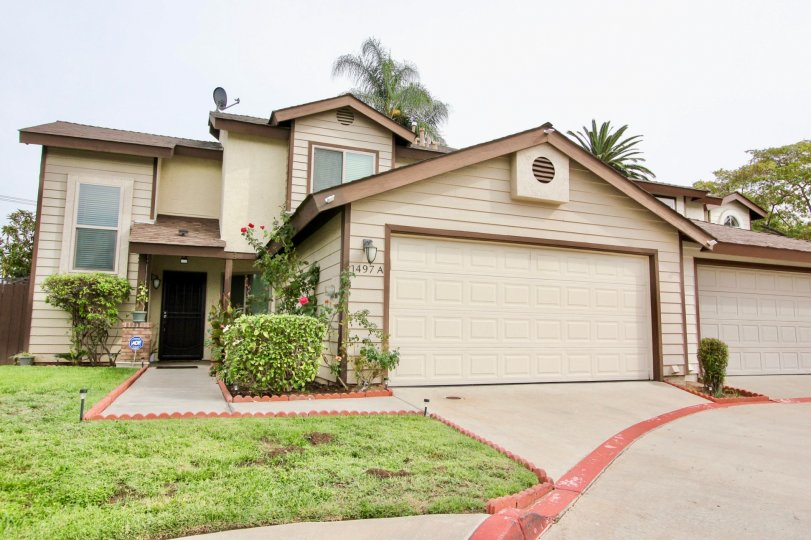 A independent house in Rancho Granite Hills with closed doors and garden infron tof the brown main door.