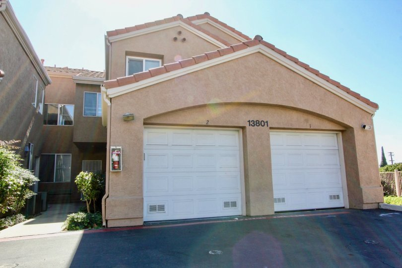 Two white garages attached to residence with driveway at The Knolls in El Cajon CA