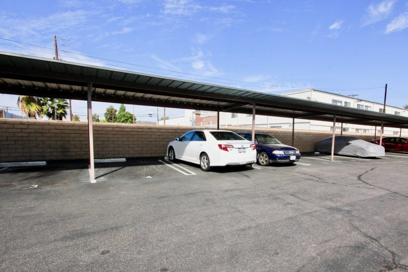 View of a parking space in The Willows, El Cajon, California showing different cars parked.