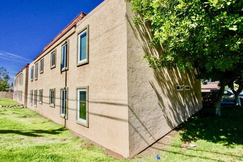 Two story brown condominiums near grass field inside Washington Heights in El Cajon CA