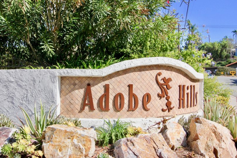 The neighborhood sign the Adobe Hills community on a sunny day of with surrounding shubbery