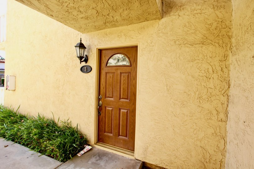 Hampton Place, Escondido, California - A beautiful wood door in a plaster wall with lantern style lighting