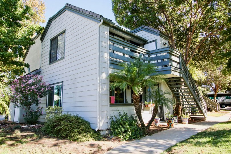 A split level home with white siding, blue deck and staircase in Hidden Glen, Escondido California