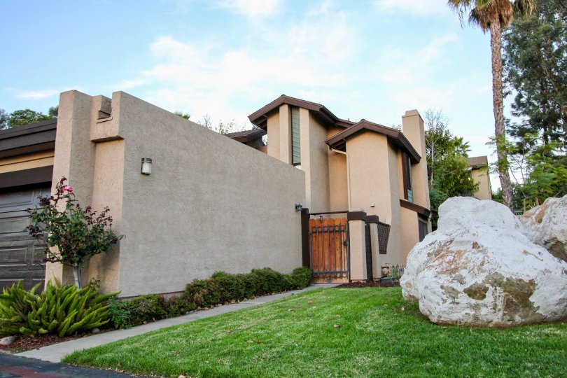 Large boulders on a lush green yard near a security gate at Skylark Terrace in Escondido California