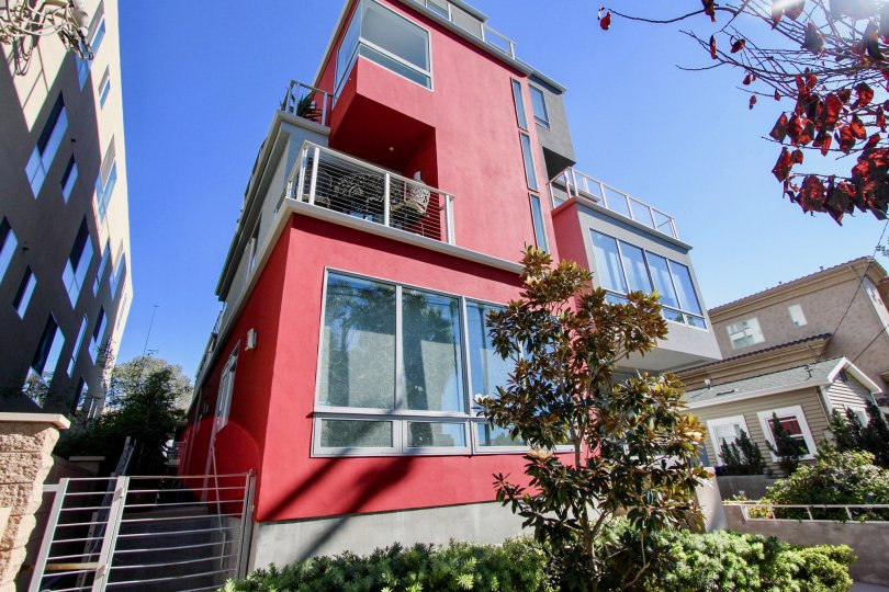Red 5x5 Loft building in Hillcrest, California with trees on a bright sunny day