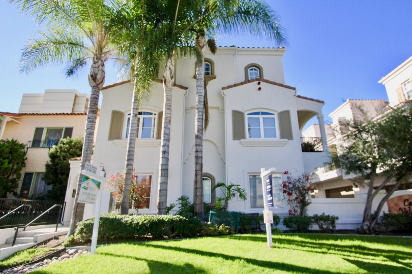 A traditional three-storey residence with large trees in the front yard in Casa Valencia community.