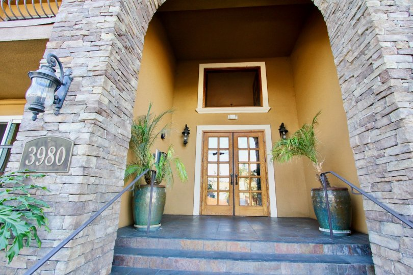 grsnd entrsnce with stone collumns and woody look and brown walls and plants