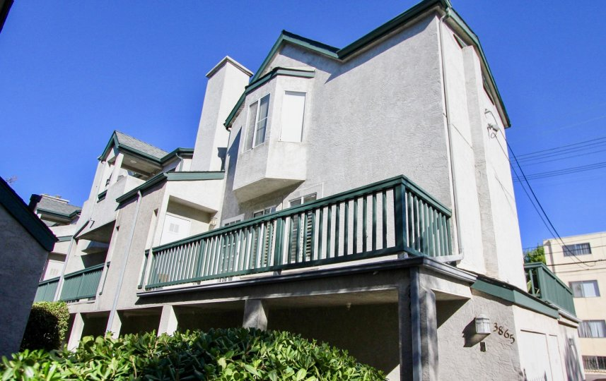 A sun-drenched street scene and balcony in the Eucalyptus neighborhood of Hillcrast, California