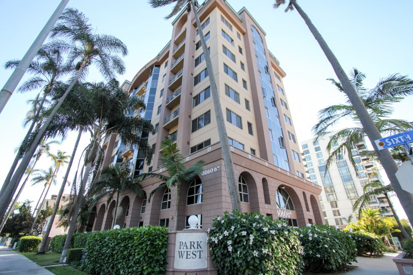 The exterior of a high-rise complex at the corner of Sixth in thr Park West section of Hillcrest, CA with landscaped shrubs, flowers and palms.